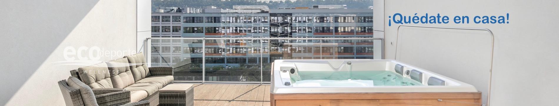 Jacuzzi Spa exterior en terraza ático con vistas a la ciudad y al bosque lejano, y cómodos sofás para relajarse.